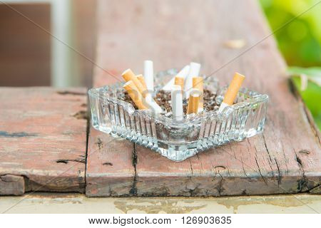 Close up of glass ash tray on the wooden plate.
