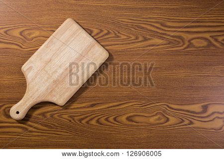 Wooden chop board on wooden table top. Top view.