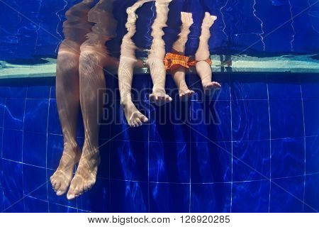 Happy people relaxing with fun. Funny underwater photo mother with kids legs in aqua park swimming pool. Family lifestyle and summer children water sports activity and lessons with parents on vacation