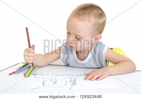 Little boy drawing with crayons. Isolated on a white background.