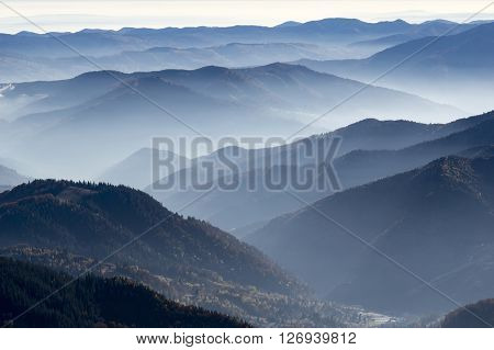 Valley fog on autumn crest silhouette of mountains.