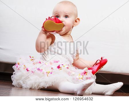 Infant in time of teething. Sweet cute baby girl biting chewing red shoe. Young adorable child wearing white dress.