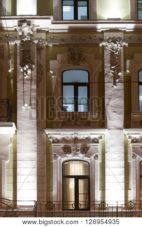 Evening lighting the front of the building in the neoclassical style. Windows stucco tile. Moscow.