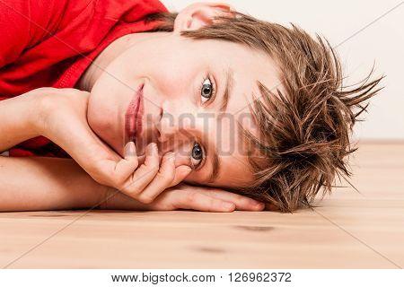 Close Up On Head Of Happy Boy Lying On Floor