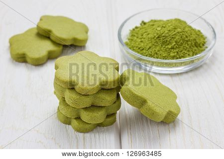 Homemade matcha green tea shortbread cookies on wooden table