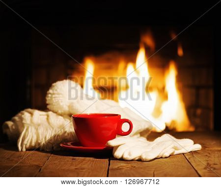 Red Cup Scarf, Gloves And Cap On Wooden Table Near Fireplace.