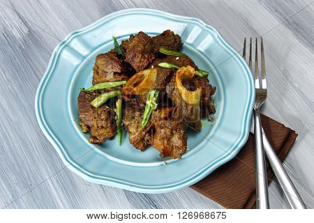 Mutton fry on a plate on grey background.
