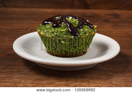 Homemade fresh muffin baked with wholemeal flour with spinach desiccated coconut and chocolate glaze delicious healthy dessert or snack