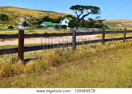 Rural ranch surrounded by grasslands and a rustic wooden fence