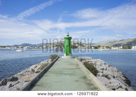 promenade with calm sea and small lighthouse