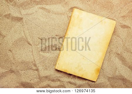Reading favourite classic old book on summer vacation beach holiday top view of a book cover as copy space in warm beach snow.