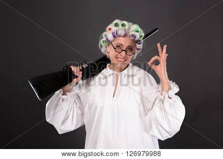 Happy grandmother posing in studio over grey background. Pretty woman in glasses in defence giving okay sign in studio.