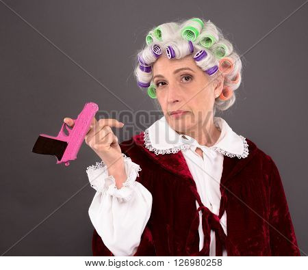 Grandmother with rollers on posing with pink plastic gun over grey background. Serious lady looking at camera in studio.