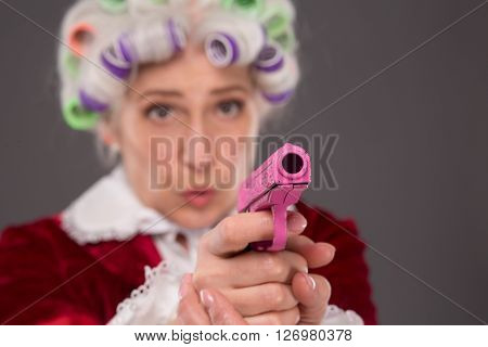 Close-up portrait of pink plastic gun in senior woman's hands. Senior lady aiming at something or someone in studio.