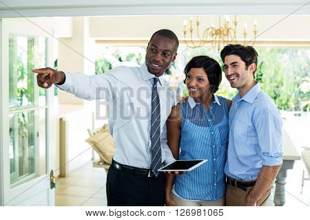 Real estate agent pointing while showing the house to couple