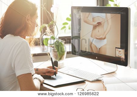 Side view portrait of attractive woman retoucher working on the computer hand drawing on graphic tablet. Young Caucasian female photographer with red hair in white T-shirt editing photos at home