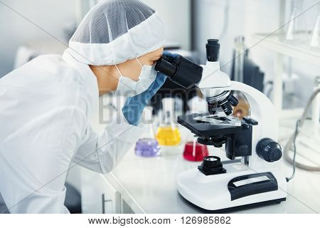 Chemical Laboratory Scene: Young Phd Student Scientist Girl Looking Through A Microscope. Side View