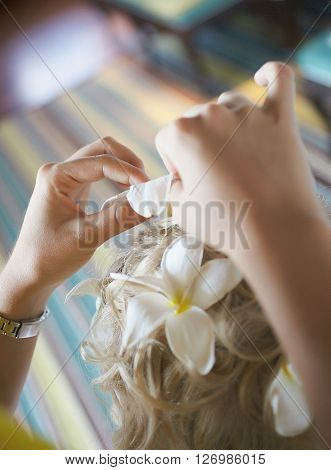 Beautiful cute blond bride doing hair with flowers before wedding day. Long lashes white flowers smilling and happy. Perfect wedding preparation.
