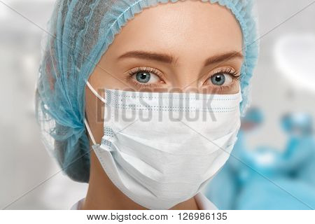 Headshot Of Young Female Surgeon In Blue Cap And White Surgical Mask Looking At The Camera With Coll