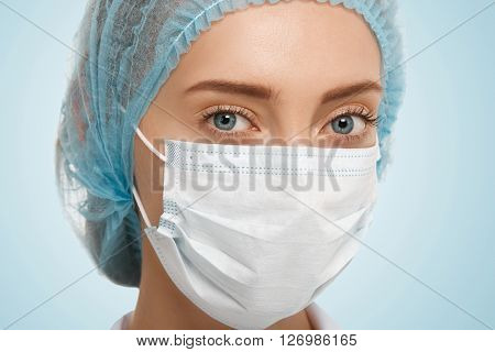 Close Up View Of Cute Caucasian Blue-eyed Woman Doctor Wearing Blue Cap And White Facemask Looking A