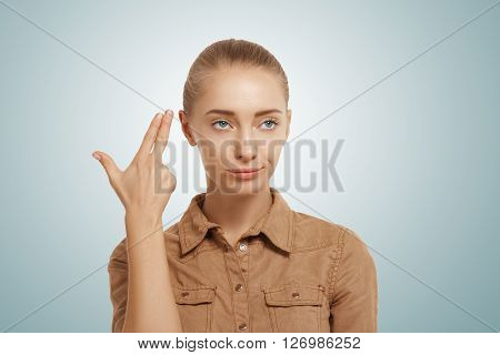 Isolated headshot of young woman committing suicide with finger gun gesture. Portrait of bored girl shooting herself making finger pistol sign against blue wall background. Human face expressions poster