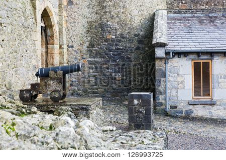 Old cast iron cannon in a castle courtyard