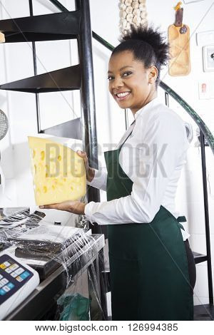 Side View Of Happy Saleswoman Holding Cheese At Counter
