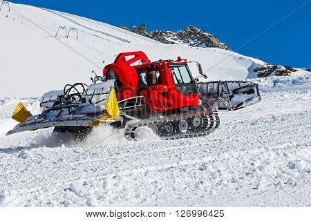 Photo of red snowcat in action on the ski poster