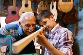 Small family business and traditions: old grandpa with grandson in lute maker shop. The senior artisan teaches to the boy how to chisel wood to make a music instrument. The kid looks carefully at his work poster
