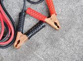Black and red copper clamp with jumper cable for car battery charging selective focus poster