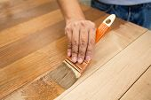 Applying protective varnish on a wooden furniture poster