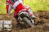 Rear view of motocross bike rider who drifts around a white painted tire stack. The rear wheel is digging deep in the sand and throws dirt in the air. poster