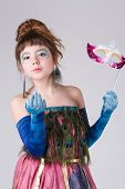 the amusing little charming girl in a beautiful unusual dress in an image of a firebird poses with a mask poster