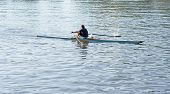 one single sculler / rower / oarsman on a river or lake rows in small sport boat poster