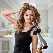 attractive woman blows dry her hair with hairdryer poster