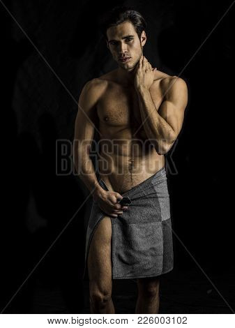 Portrait Of Naked Handsome Young Man With Languishing Look Covering Crotch With A Towel, Against Bla