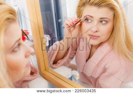 Woman In Bathroom Plucking Eyebrows Depilating With Tweezers, Looking At Mirror. Girl Tweezing Remov
