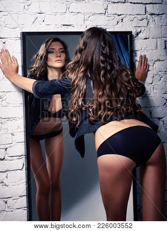 Portrait Of A Beautiful Sexy Young Girl Looking Into Mirror. Rear View