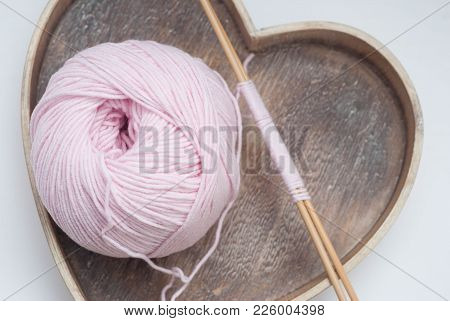 Pink Cotton Wire Bobbin With Needles For Knitting Over Wooden Heart Box For Hobby And Handmade.