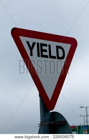 Close Up Of A Yield Road Sign On A Cloudy Day