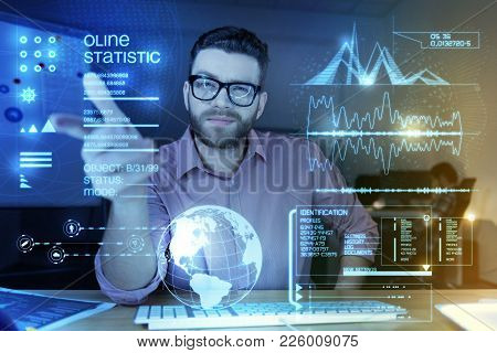 Confident Programmer. Clever Qualified Young Programmer Pointing To The Transparent Screen Of His Mo
