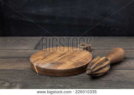 Wooden Juicer On A Dark Wooden Table With Chopping Board. Space For Montage Product.