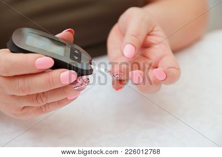 Glucometer. Woman Checks Blood Sugar Level For Diabetes, Insulin Levels