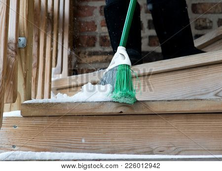 Young Woman Is Sweeping Snow From Stair Steps  With Broom