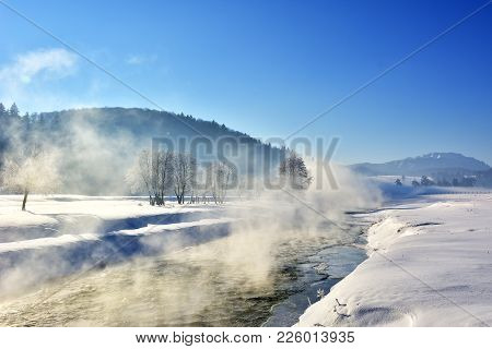 Morning Steam Fog Above River. Winter Landscape. Frosty Day On The River. Part Of The River Is Cover