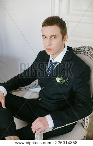Portrait Of Beautiful And Stylish Modern Young Bridegroom In Suit Decorated Flowers Boutonniere.