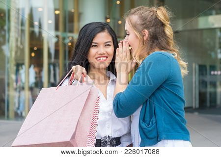 Closeup Portrait Of Young Beautiful Woman Whispering Secret To Smiling Asian Girlfriend Who Is Holdi