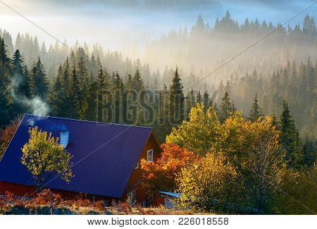 Early Morning Fog And First Morning Sun Rays Over The Autumn Slopes Of Carpathian Mountains And Unre