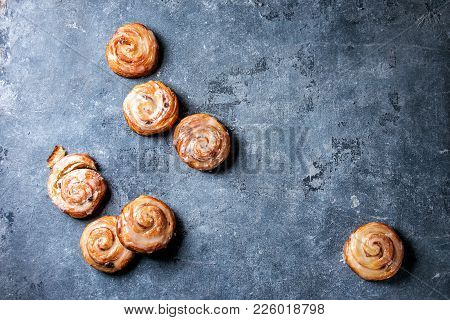 Homemade Glazed Puff Pastry Cinnamon Rolls With Custard And Raisins Over Blue Texture Background. To