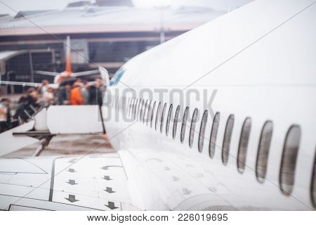 Side View Of Modern White Airplane Hull With Multiple Portholes During Boarding On A Rainy Day; With